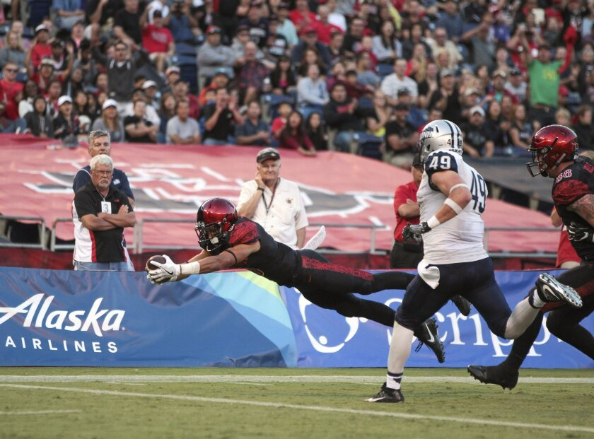 The Aztecs' Mikah Holder dives for a touchdown as New Hampshire's Ryan Farrell runs toward him in the second quarter.