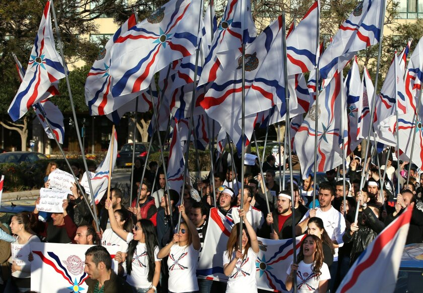 Assyrians wave their community's flag as they protest with others in solidarity with Christians abducted in Syria and Iraq by Islamic State militants, in downtown Beirut, Lebanon Saturday, Feb. 28, 2015. The Islamic State group, which has repeatedly targeted religious minorities in Syria and Iraq, abducted more than 220 Assyrians this week in northeastern Syria. (AP Photo/Hussein Malla)