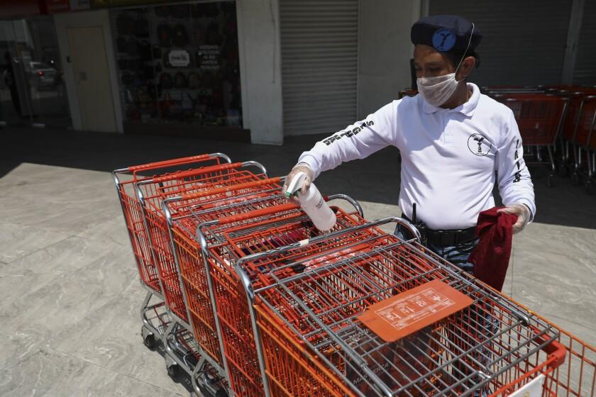 Un hombre con una mascarilla desinfecta carritos de supermercado para evitar contagios \