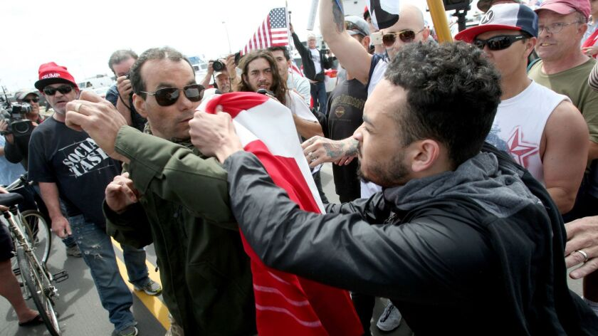 A marcher, left, and a protestor to the march, right, scuffle during the Make America Great Again Ma