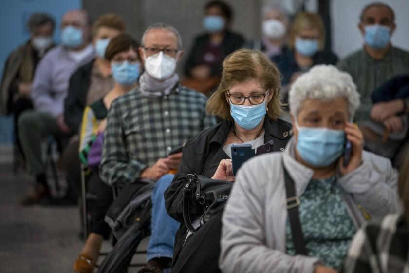 Personas esperan un momento después de recibir la vacuna de AstraZeneca contra el coronavirus