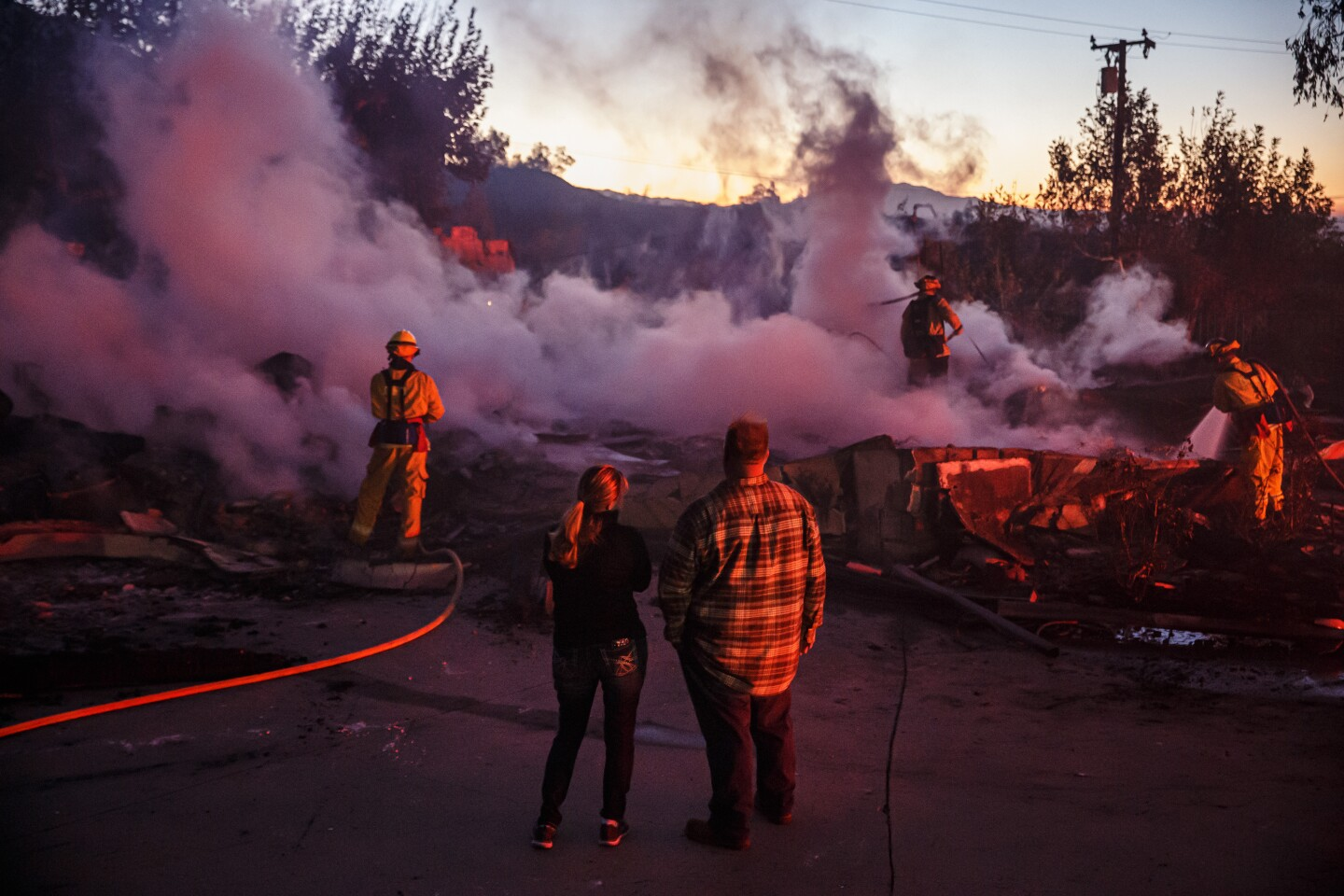 SAN BERNARDINO, CALIF. -- THURSDAY, OCTOBER 31, 2019: Family members look on as firefighters mop up a burned down home destroyed by the Hillside Fire in San Bernardino, Calif., on Oct. 31, 2019. (Marcus Yam / Los Angeles Times)
