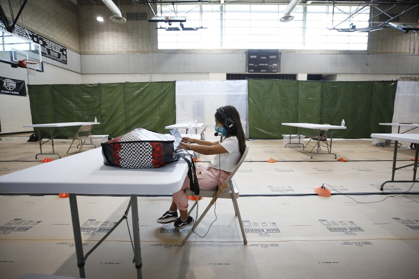 A lone young girl in a mask and a headset works on a computer while sitting at a folding table inside a recreation center