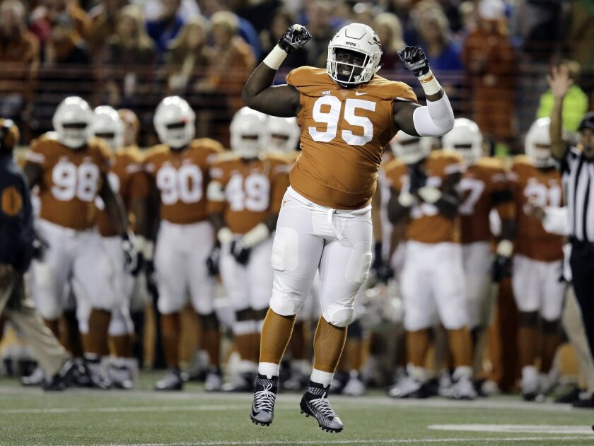 Texas defensive tackle Poona Ford (95) celebrates after he sacked Kansas quarterback Ryan Willis for a loss during the first half of an NCAA college football game, Saturday, Nov. 7, 2015, in Austin, Texas. (AP Photo/Eric Gay)