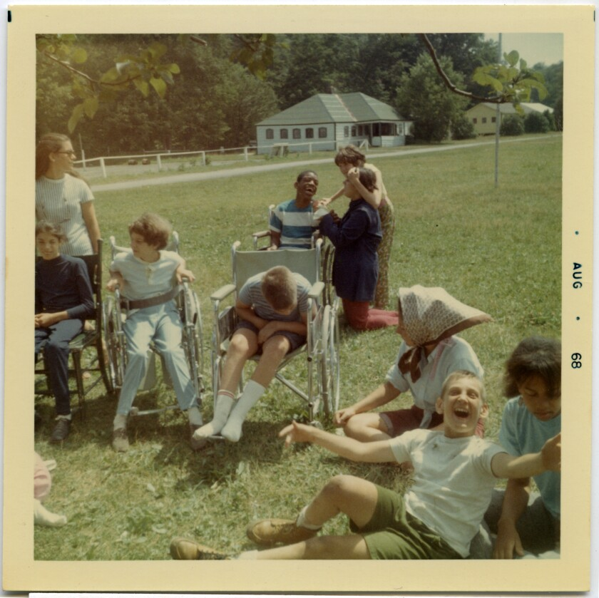Several children using wheelchairs and others are seen in the sunshine on a grassy field in a 1968 photo.
