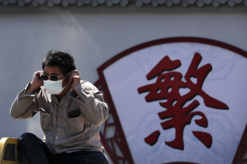 A man puts on his face mask in Beijing