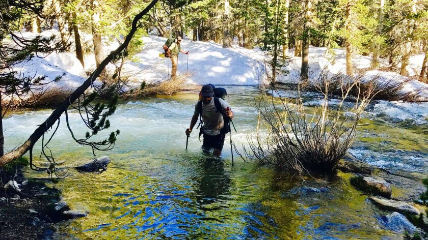 In this Tuesday, June 6, 2017, photo, Jake Gustafson crosses a creek along the Pacific Crest Trail n