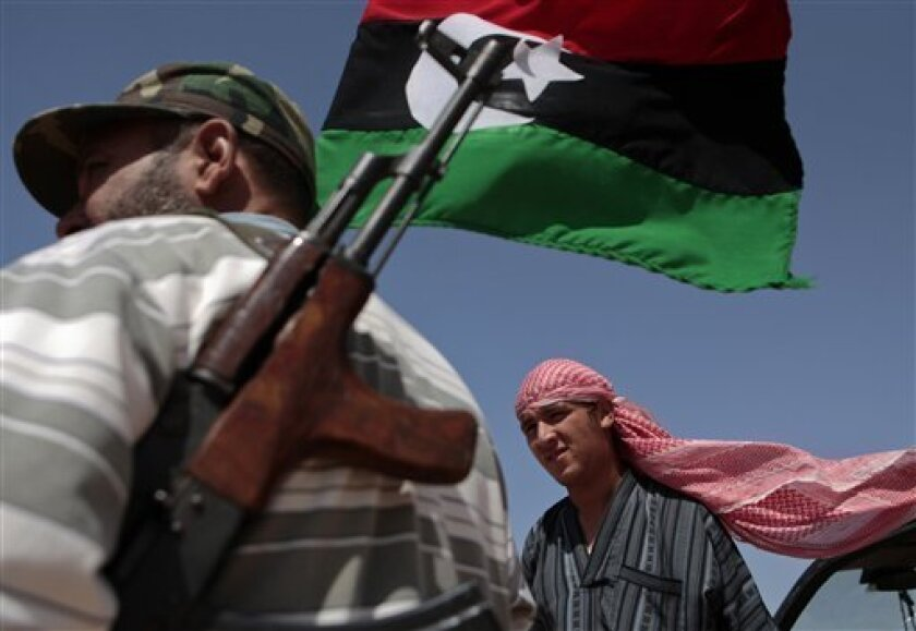Libyan rebel fighters Omar Hussein, left, and Aaron Isa, right, stand guard under a rebel flag at the southern front line of the city of Misrata, Libya Thursday, June 9, 2011. On Wednesday pro-Gadhafi forces renewed their shelling near the western city of Misrata, killing 10 rebel fighters and on T