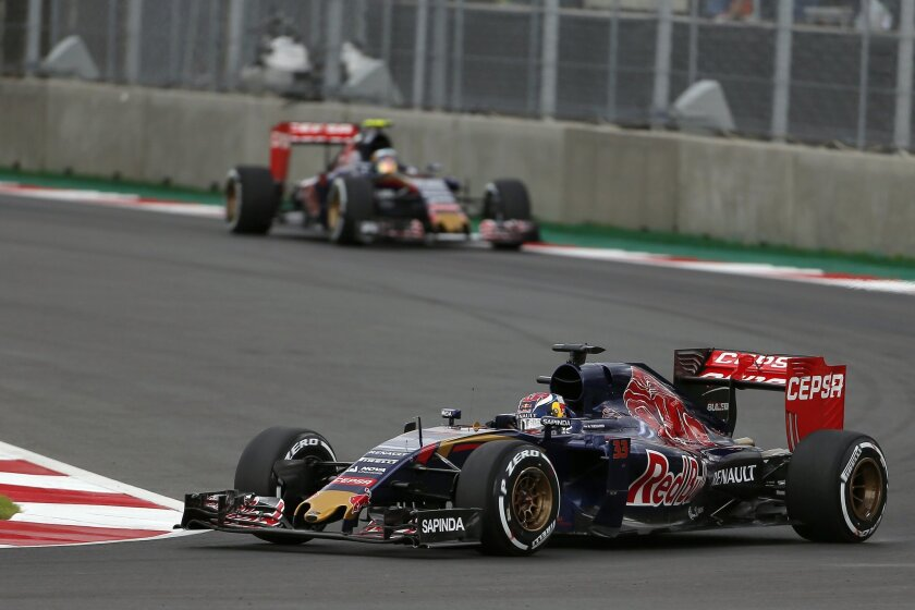 Toro Rosso driver Max Verstappen of the Netherlands, rides his car followed by his teammate, driver Carlos Sainz of Spain during qualifying for the Formula One Mexico Grand Prix auto race at the Hermanos Rodriguez racetrack in Mexico City, Saturday, Oct. 31, 2015. (AP Photo/Eduardo Verdugo)