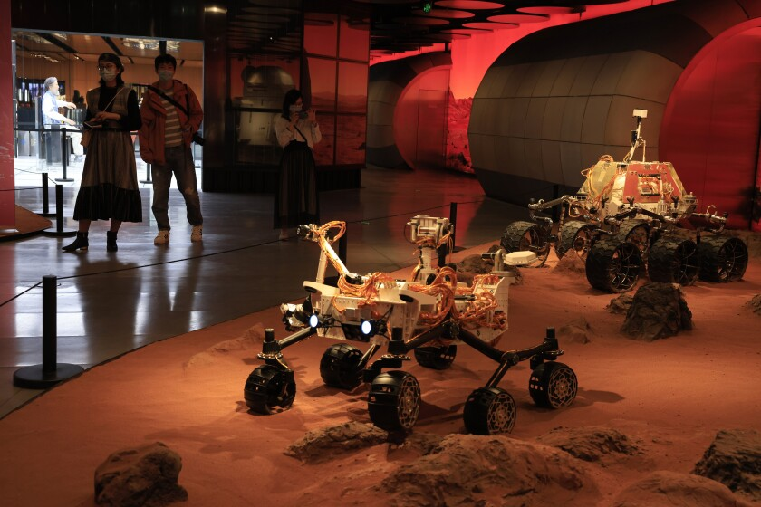 Visitors pass by an exhibition depicting rovers on Mars in Beijing