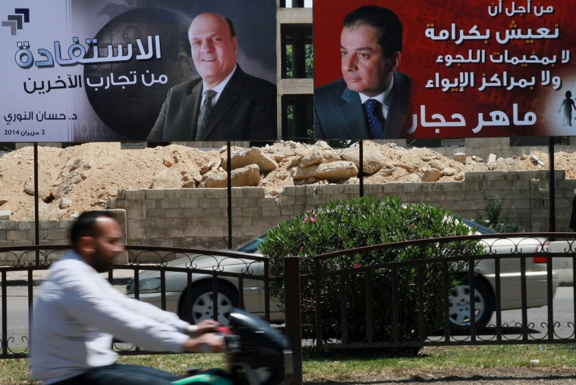 """FILE - This Monday, May 12, 2014 file photo, Syrian people drive by campaign posters of presidential candidates in Damascus, Syria. Despite the presence of challengers on this year's ballots, there's little doubt that Bashar Assad will secure a third seven-year term. The Arabic, right, reads, """"For us to live with dignity, neither in refugee camps nor in shelters, Maher Hajjar."""" The one at left reads, """"There's a benefit in trying others, Hassan al-Nouri, June 3, 2014.""""(AP Photo, File)"""