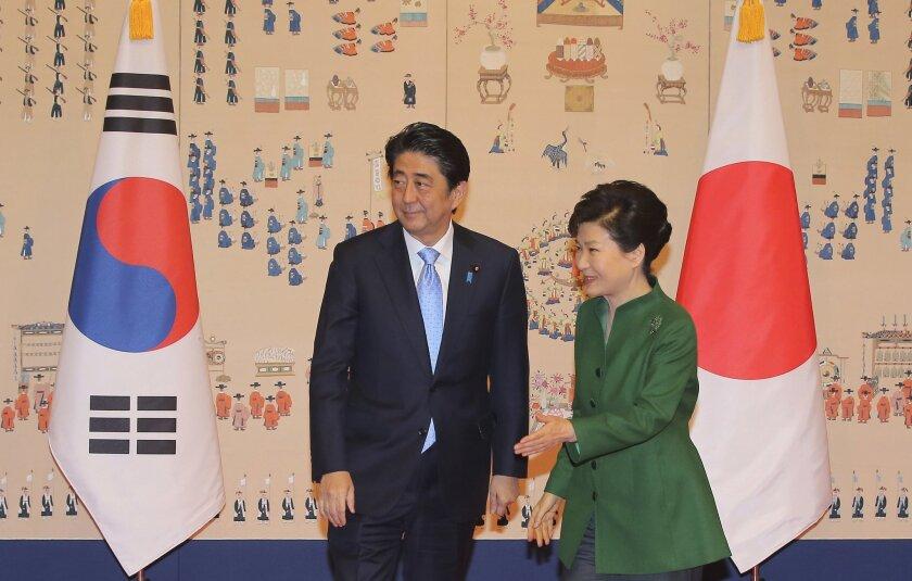 South Korean President Park Geun-hye, right, escorts Japanese Prime Minister Shinzo Abe before their meeting at the presidential Blue House in Seoul, South Korea, Monday, Nov. 2, 2015. (Lee Jung-hun/Yonhap via AP) KOREA OUT
