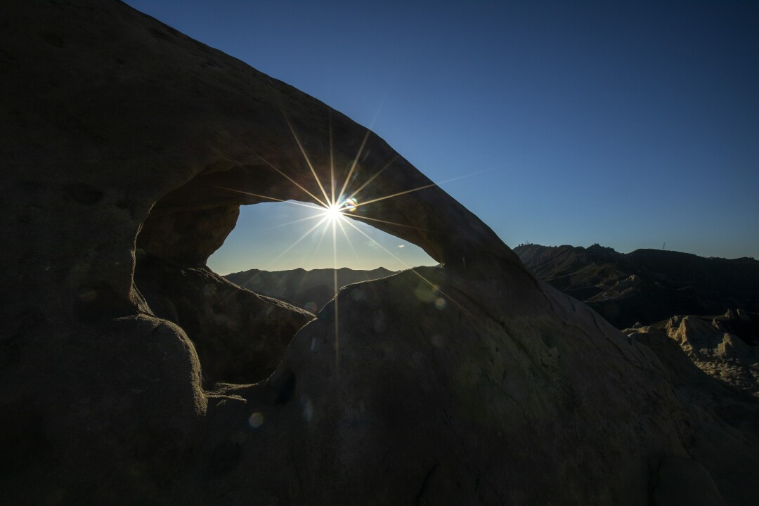 A stone arch frames the sunset in Corral Canyon.