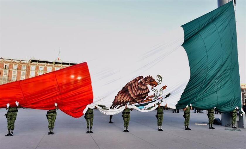 Soldados sostienen una bandera nacional hoy, martes 2 de octubre de 2018, en la ceremonia de izamiento a media asta de la bandera nacional para conmemorar los 50 años del movimiento estudiantil y la matanza de Tlatelolco de 1968, en Ciudad de México (México). EFE