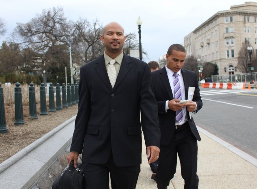 Former Northwestern quarterback Cain Colter, right, and union leader Ramogi Huma arrive on Capitol Hill.