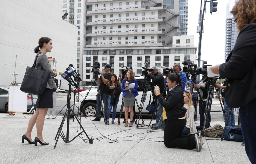 FILE - In this Tuesday, March 19, 2019, file photo, attorney Robyn Barnard, left, speaks to reporters in front of immigration court in San Diego. A federal judge ruled Tuesday, Jan. 14, 2020, that some asylum-seekers who fear waiting in Mexico for U.S. immigration court hearings must have access to attorneys before and during a key interview to determine if they can stay in the U.S. until their claims are decided. (AP Photo/Gregory Bull, File)
