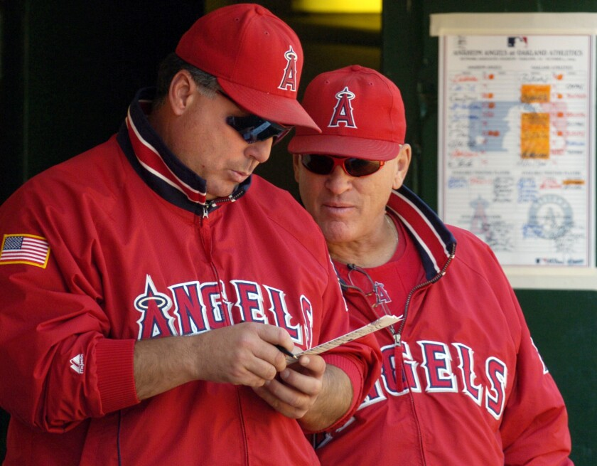 Angels Manager Mike Scioscia and then-bench coach Joe Maddon look over a lineup card on Oct. 3, 2004.