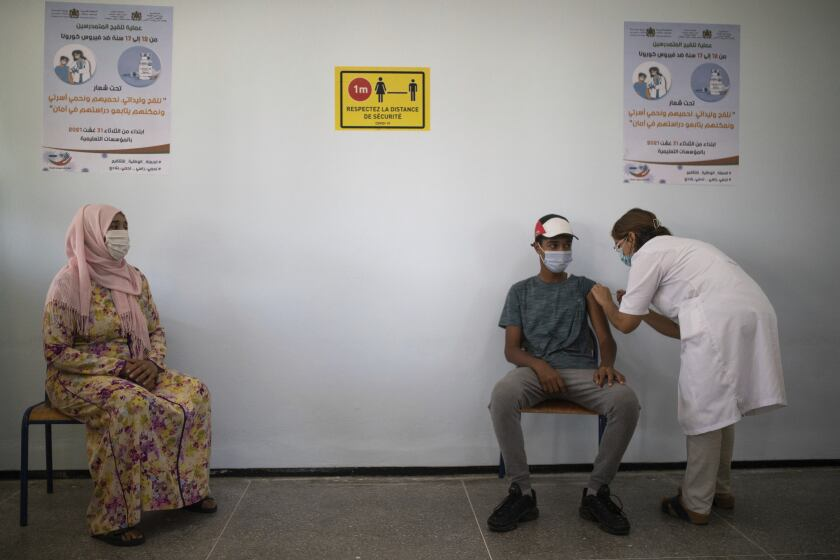 A mother accompanies her son to receive his COVID-19 vaccine as Morocco launches a campaign to vaccinate 12-17 year olds before the start of the school year, in Rabat, Morocco, Tuesday, Aug. 31, 2021. (AP Photo/Mosa'ab Elshamy)