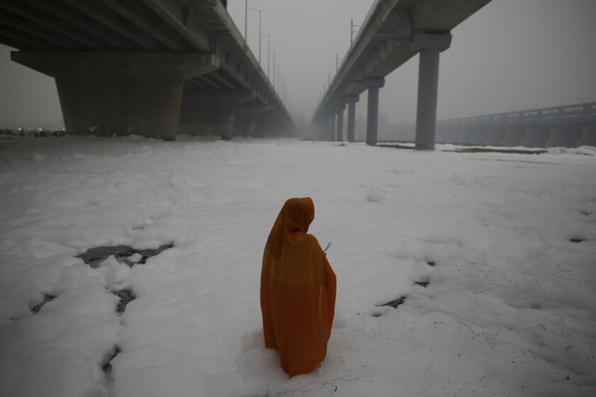 In this Saturday, Nov. 2, 2019, file photo, an Indian Hindu devotee performs rituals in Yamuna river, covered by chemical foam caused due to industrial and domestic pollution, during Chhath Puja festival in New Delhi, India. During Chhath, an ancient Hindu festival, rituals are performed to thank the sun god for sustaining life on earth. (AP Photo/Altaf Qadri, File)