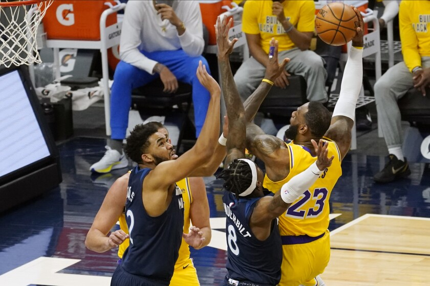 Los Angeles Lakers' LeBron James (23) shoots as Minnesota Timberwolves' Karl-Anthony Towns, left, and Jarred Vanderbilt (8) defend in the first half of an NBA basketball game, Tuesday, Feb. 16, 2021, in Minneapolis. (AP Photo/Jim Mone)