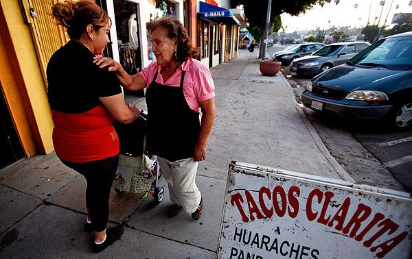 Clarita Trujillo, right, greets Alma Rodriguez in front of Tacos Clarita in El Sereno. Trujillo is very friendly and greets most passersby with a smile and conversation. See full story