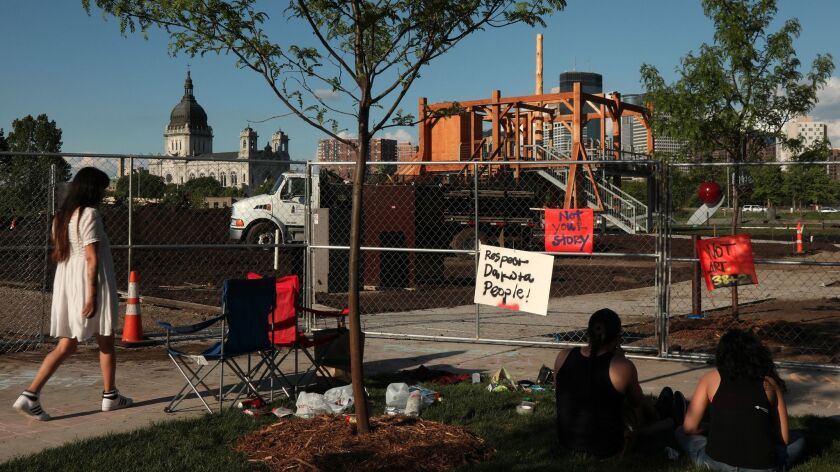 """Protesters stand outside the Minneapolis Sculpture Garden, the site of Sam Durant's """"Scaffold,"""" in l"""