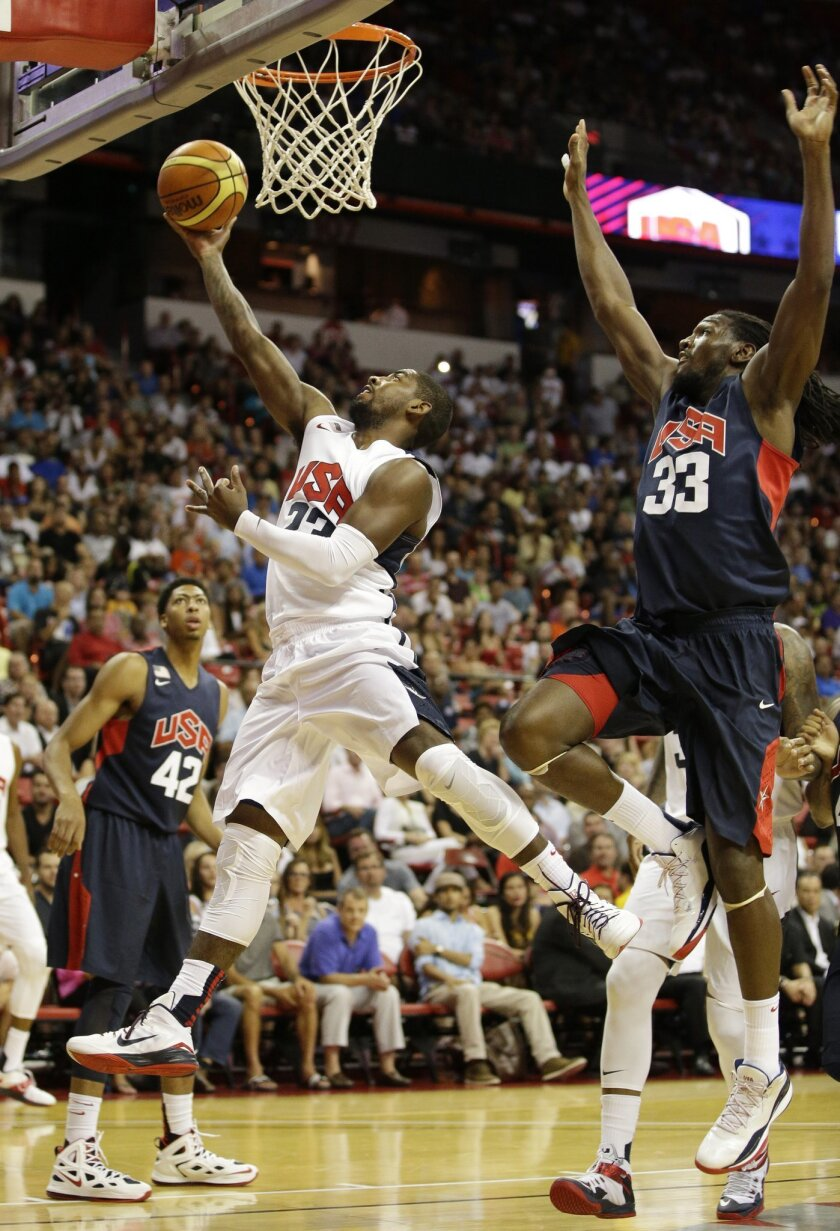 Cleveland Cavaliers' Kyrie Irving, left, goes up for a shot against Denver Nuggets' Kenneth Faried during the USA Basketball Showcase game Friday, Aug. 1, 2014, in Las Vegas. (AP Photo/John Locher)