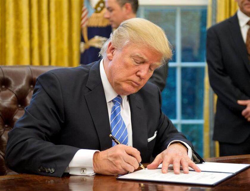 El presidente estadounidense, Donald Trump (c), firma la orden ejecutiva para sacar a EE.UU. del acuerdo comercial TPP (Acuerdo de Asociación Transpacífico), en el Despacho Oval de la Casa Blanca, en Washington, Estados Unidos, hoy, 23 de enero de 2017. EFE/POOL