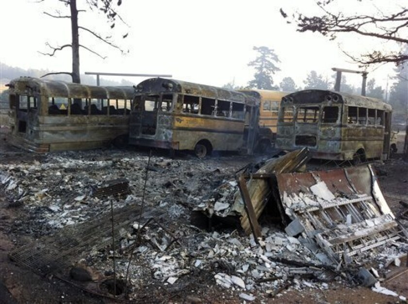 In this photo provided by Eric Peter Abramson, a line of buses are destroyed after a wild fire passed through Gold Hill, Colo. on Tuesday, Sept. 7, 2010. Gov. Bill Ritter declared a state of emergency Tuesday as officials nearly doubled the fire's estimated size to more than 7,100 acres, or 11 square miles. At one point the plume from the fire could be seen in Wyoming, 90 miles to the north. (AP Photo/Eric Peter Abramson) NO SALES MANDATORY CREDIT