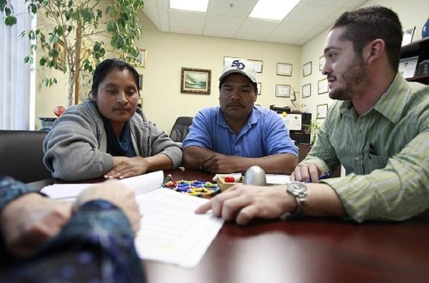 Armondo Campos (right) helped Agustin and Felicisima Garcia as they  signed documents modifying their home loan at Community HousingWorks' City  Heights office.