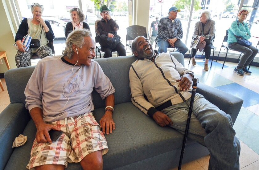 Carl Russell, 72, right, shares a laugh with Victor Quslan, 62, who are both homeless, as they relax in the community room at the Gary and Mary West Senior Wellness Center on Tuesday, October 15, 2019 in San Diego, California.