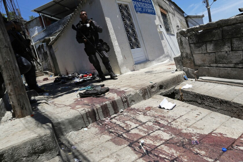A Brazilian police officer stands by a blood-soaked walkway during a security operation in the Juramento slum in Rio de Janeiro.