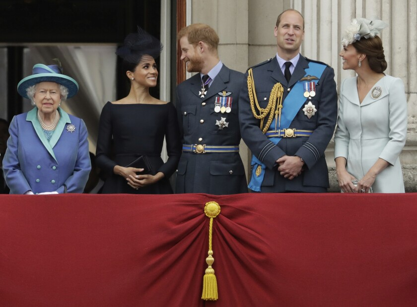 FILE - In this file photo dated Tuesday, July 10, 2018, Britain's Queen Elizabeth II, and from left, Meghan the Duchess of Sussex, Prince Harry, Prince William and Kate the Duchess of Cambridge, watch as Royal Air Force aircraft pass over Buckingham Palace in London. Prince Harry will attend the funeral for Prince Philip on Saturday April 17, the first time that Harry will come face to face with the royal family since he and his wife Meghan, the Duchess of Sussex, stepped away from royal duties last March and moved to California with their young son, Archie.(AP Photo/Matt Dunham, FILE)