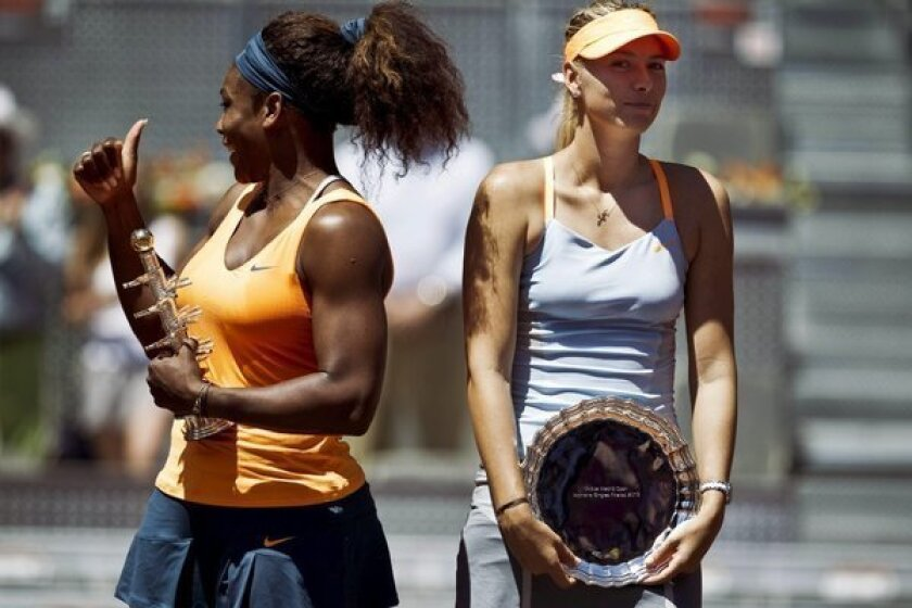 Serena Williams poses with a trophy after beating Maria Sharapova in the Madrid Open final May 12, 2013.