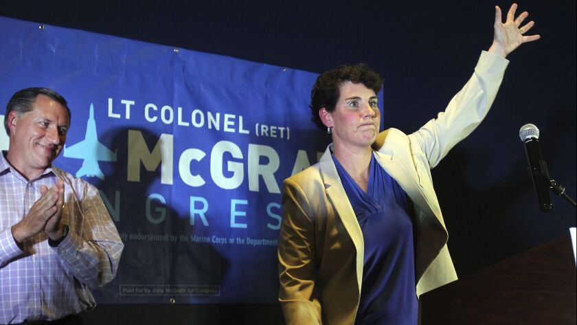 Amy McGrath, right, with her husband, Erik Henderson, waves to supporters after being elected as the Democratic candidate for Kentucky's 6th Congressional District in Richmond, Ky.