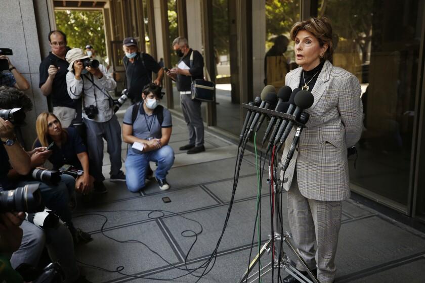 A woman speaks behind multiple microphones as media members watch