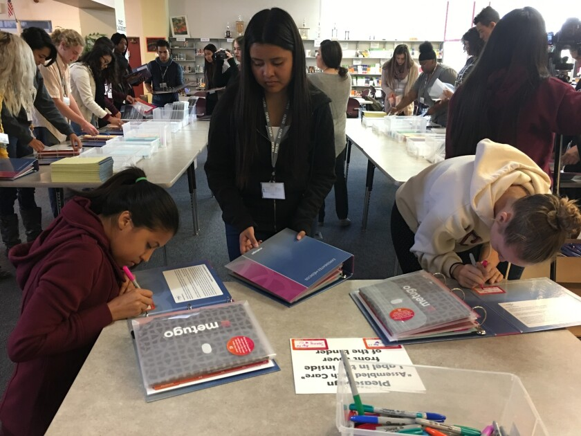 At a Nov. 1 Metugo binder-making party, students from Kearny Digital Media and Design High School help create binders to organize medical records for breast cancer patients.
