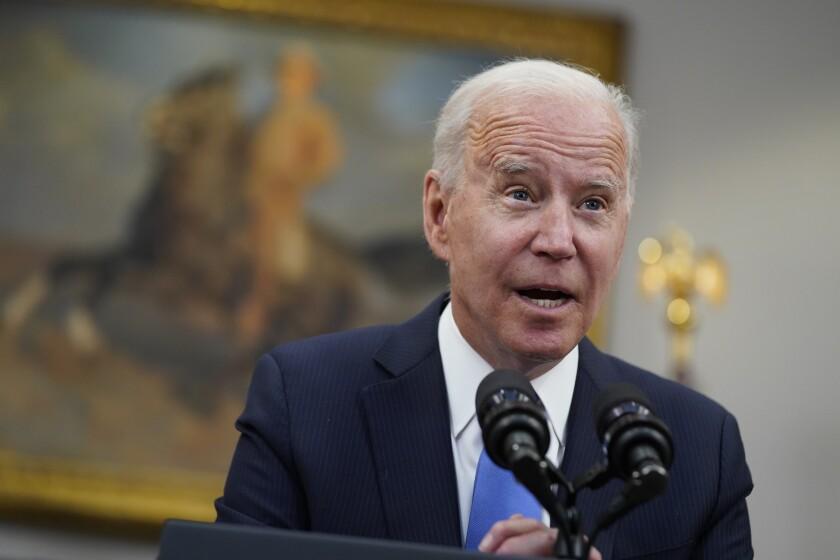 President Biden speaks into microphones.