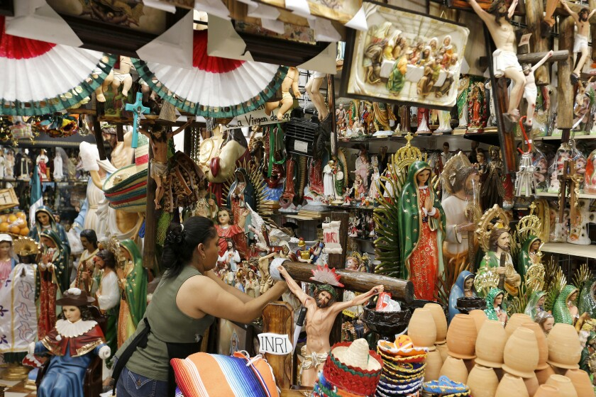 A worker displays Christian figures at her stall at El Mercado in Boyle Heights. El Mercado has been around since 1968 and largely serves the Latino immigrant community in Boyle Heights.