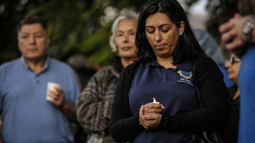 Lynwood City Councilwoman Aide Castro holds a candle at a protest against the closure of St. Francis Medical Center.