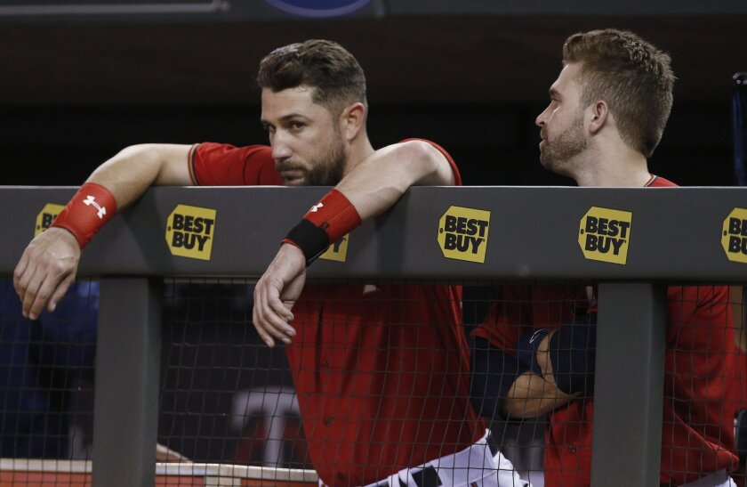 Minnesota Twins' Trevor Plouffe, left, and Brian Dozier stand by the dugout fence in the waning moments of the team's 9-3 loss to the Toronto Blue Jays in a baseball game Friday, May 20, 2016, in Minneapolis. The Twins now own the worst record in the majors following a win by Atlanta over Philadelphia. (AP Photo/Jim Mone)