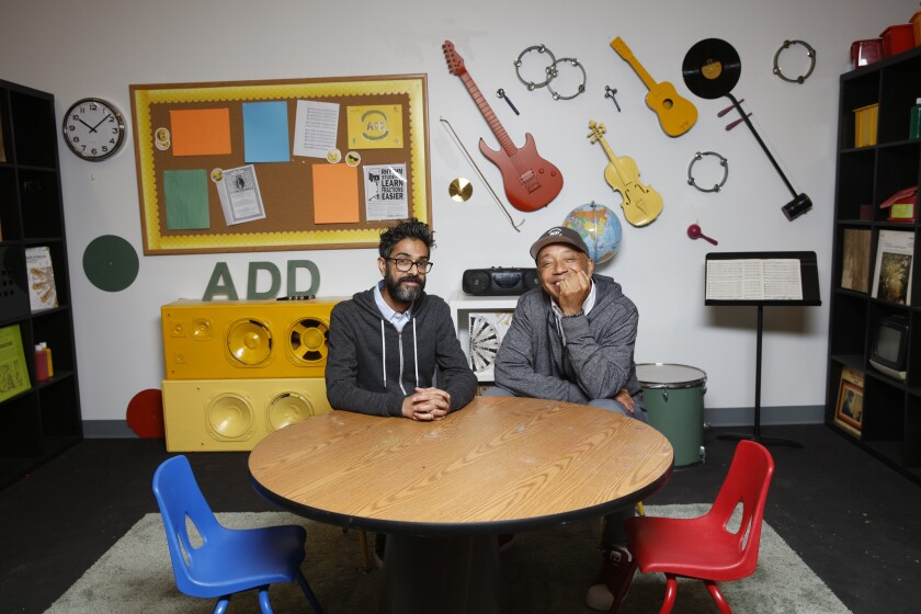 """Hip-hop mogul Russell Simmons, right, and Sanjay Sharma, president and CEO of Simmons' new company, All Def Digital, on the set of their original show """"Arts+Raps"""" in the company's downtown Los Angeles office."""