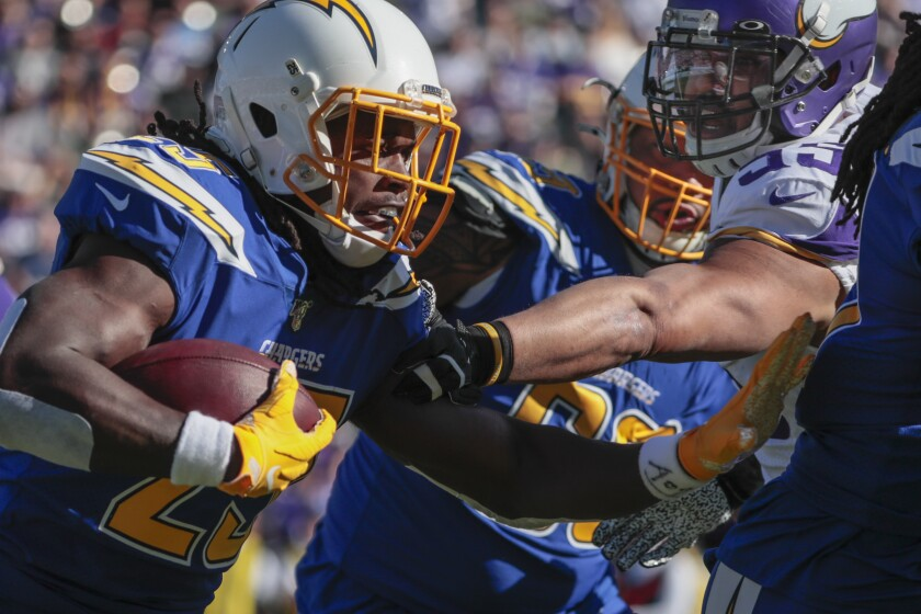 Chargers running back Melvin Gordon (25) rushes past Minnesota Vikings outside linebacker Anthony Barr (55) during a first half drive at Dignity Health Sports Park on Sunday.