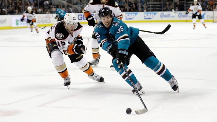 Sharks center Logan Couture reaches for the puck as Ducks defenseman Sami Vatanen pressures him during the second period of a game on March 18.