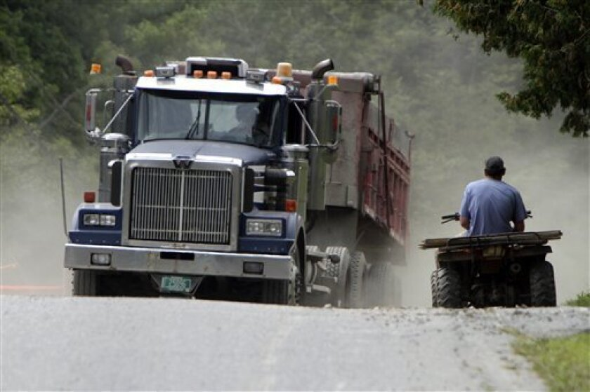 An ATV waits for a truck delivering gravel to repair roads on Thursday, Sept. 1, 2011 in Bethel, Vt. With hundreds of roads and about 30 bridges impassable, ATVs are getting folks where they need to go and they're ferrying supplies, food and gasoline for portable generators to stranded residents.(AP Photo/Toby Talbot)