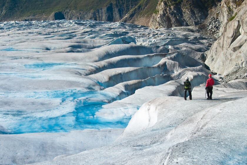 Two glacier trekkers stand on the Mendenhall Glacier in southeast Alaska.