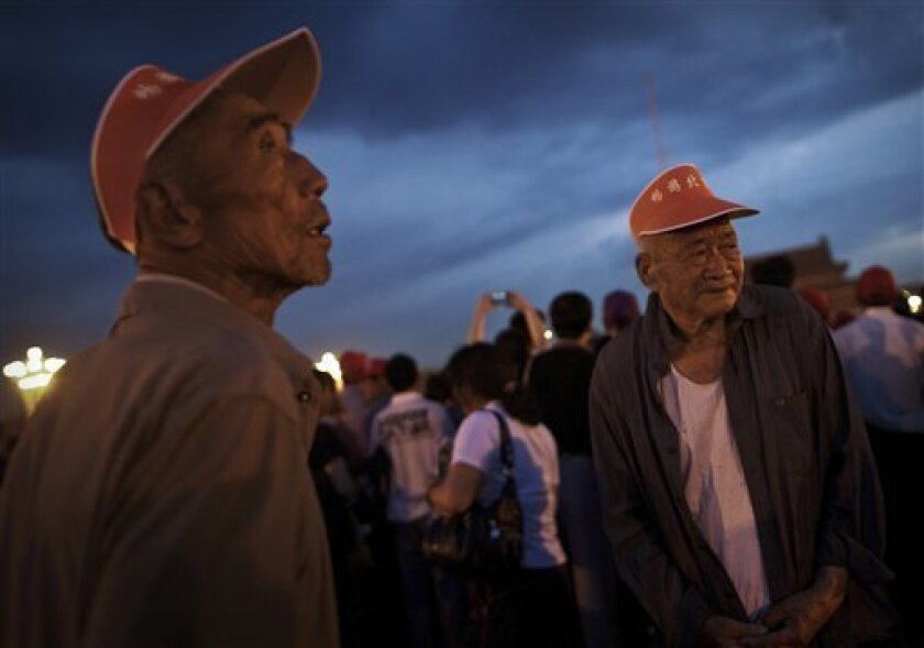 Elderly Chinese wait in the dawn for the flag raising ceremony at the Tiananmen Square in Beijing, China Saturday, June 4, 2011. June 4 marked the anniversary of the deadly 1989 crackdown on pro-democracy protestors in Beijing. (AP Photo/Andy Wong)
