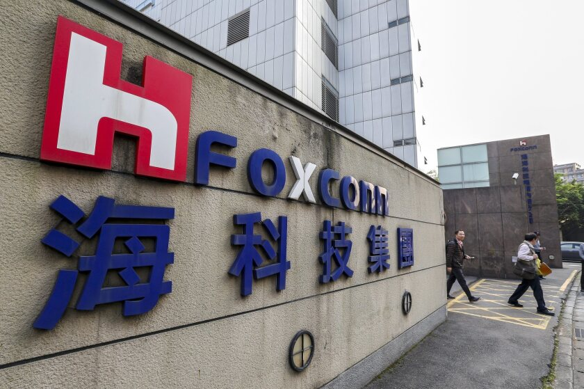 People walk past Foxconn offices in Taipei, Taiwan, on March 30.