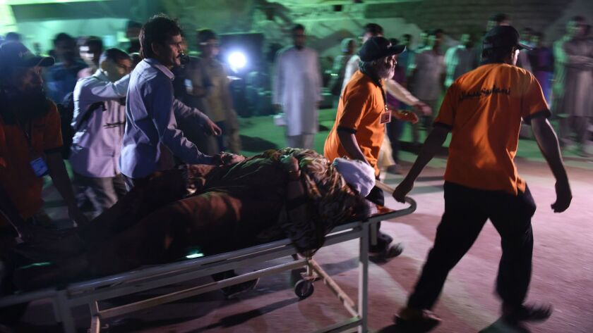 A Pakistani rescuer worker helps the victim of an attack on a Sufi shrine in the city of Karachi on Saturday.