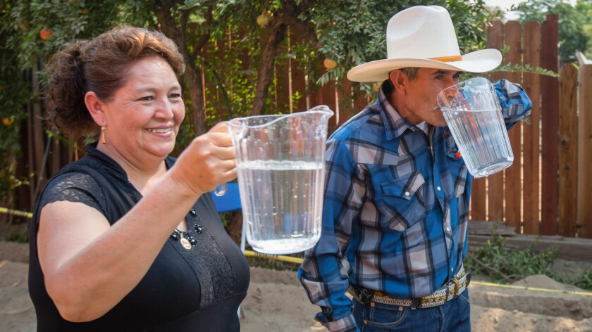 Guillermina Avila Ramirez and her husband, Leonicio Ramirez, enjoy cool water shortly after it was running for the first time in three years.
